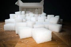 Macro shot of sugar cubes next to carton box on wooden table. Unhealthy food sweetener, sweet crystal cubes.  stock image