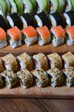 A macro shot of a sushi set of many rolls is located on a wooden cutting board on a table in the kitchen of a sushi bar. A tradit. Ional dish of Japanese cuisine stock image