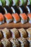 A macro shot of a sushi set of many rolls is located on a wooden cutting board on a table in the kitchen of a sushi bar. A tradit. Ional dish of Japanese cuisine stock photos