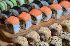 A macro shot of a sushi set of many rolls is located on a wooden cutting board on a table in the kitchen of a sushi bar. A tradit. Ional dish of Japanese cuisine stock images