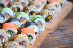 A macro shot of a sushi set of many rolls is located on a wooden cutting board on a table in the kitchen of a sushi bar. A tradit. Ional dish of Japanese cuisine royalty free stock photo