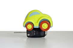 Macro shot of a toy car. Shot of a Toy plastic car with a car key attached. The toy car has no branding/manufacturer logos or company names. The car key fob has stock image