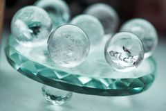 Macro shot of transparent crystal balls with colorful ornaments and sun reflections in it. On turquoise glass pad. Fortune telling. Love, money, luck, success Stock Image