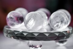 Macro shot of transparent crystal balls with colorful ornaments and sun reflections in it. On turquoise glass pad. Fortune telling. Love, money, luck, success Stock Photos