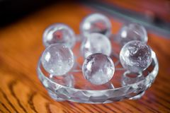 Macro shot of transparent crystal balls with colorful ornaments and sun reflections in it stock photo