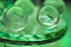 Fortune telling. Love, money, luck, success. Macro shot of transparent crystal balls with colorful ornaments and sun reflections in it, on turquoise glass pad Royalty Free Stock Photography