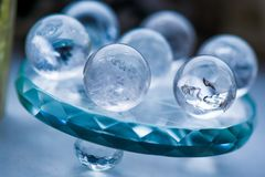 Macro shot of transparent crystal balls with colorful ornaments and sun reflections in it. On turquoise glass pad. Fortune telling. Love, money, luck, success Stock Photography