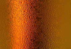 Macro shot of water droplets on orange gold colored bottle, for background with selective focus Stock Photos