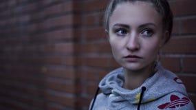Macro Shot of Woman in Gray Adidas Pull over Hoodie Near Brick Wall Stock Image