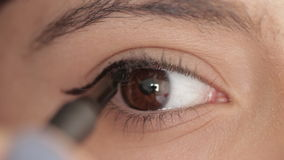 Macro shot of woman putting eye liner above her eyes stock footage