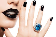 Macro shot of a woman's lips and nails painted bright color blac Royalty Free Stock Image