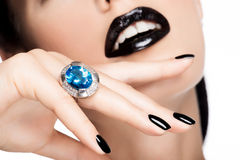 Macro shot of a woman's lips and nails painted bright color blac stock photography