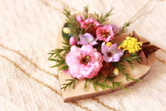 Macro shot of a wooden heart shape with colored artificial flowers Stock Image