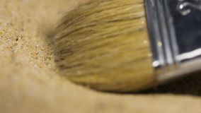 Brush cleans up future currency bitcoin real model. Macro slow motion small fur brush cleans up gently future world currency bitcoin real model from sand pile stock footage