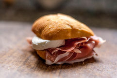 Macro of small sandwich with ham and mozzarella. On a wooden cutting board Royalty Free Stock Photo