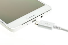 Macro Smartphone with charger cable Royalty Free Stock Photos