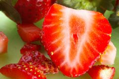 Macro strawberries cut up. On a green board Royalty Free Stock Photography
