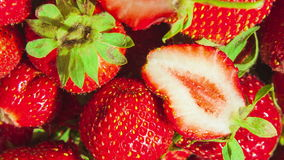 Macro of strawberries with two halfs in the center spinning in circles close up. Macro of strawberries spinning in circles close up stock video footage