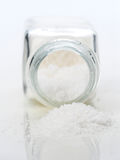 Macro takes salt out of a fallen saltshaker, isolated. On white stock image