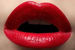 Macro tasty lips and fashion lipstick make-up. Cosmetics. Macro of fashion bright red lipstick make-up. Tasty full lips stock image