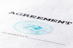 Macro Timbre bleu de bitcoin virtuel de devise sur un document financier L'accord, la signature est imprimé sur une vraie feuille Image stock