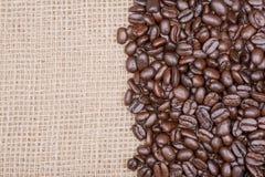 Macro tir de café foncé moyen lisse organique de rôti de haricot entier de Sumatra sur la toile de jute image libre de droits