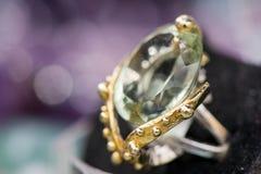 Macro tir de la bague de fiançailles argentée avec la pierre gemme verte d'améthyste, sur le fond coloré et miroitant Image stock