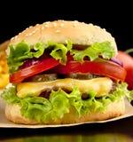 Macro tir de plan rapproché de grand cheeseburger sur le papier sur le noir photographie stock libre de droits