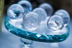 Macro tir des boules de cristal transparentes avec les ornements colorés et des réflexions du soleil dans lui Photographie stock
