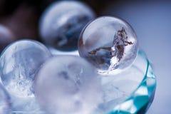 Macro tir des boules de cristal transparentes avec les ornements colorés et des réflexions du soleil dans lui Photos libres de droits