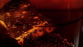 Macro tir des glaçons dans un verre de flotteur de kola dans le mouvement lent banque de vidéos