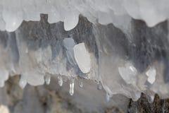Macro tir des glaçons de fonte sur un mur congelé avec des gouttelettes Images libres de droits