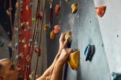 Macro tir des mains de grimpeurs saisissant les prises colorées pendant la séance d'entraînement d'intérieur photographie stock libre de droits
