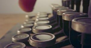 Macro tir spécial de chariot planant au-dessus de vieilles clés de machine à écrire avec la dactylographie masculine de main banque de vidéos