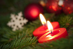 Macro of two Burning Candles with Christmas Background Royalty Free Stock Image