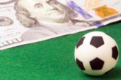 Macro Un pallone da calcio su un fondo verde e su una fattura del cento-dollaro Soldi e sport di concetto, scommettenti sul calci Fotografia Stock Libera da Diritti