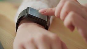 Macro van jonge vrouwens vingers wordt geschoten, die het nieuws op slimme horloges dat controleert stock videobeelden
