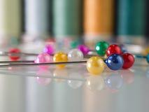 Macro van kleurrijke spelden met een achtergrond van naaiende draad wordt geschoten die stock foto