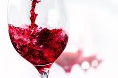 Macro vicina su di vino rosso che versa dentro a vetro Fotografia Stock