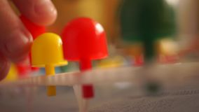 Macro video: small boy playing with multicolor kid mosaic pins on white pad stock footage