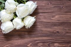 Macro view of beautiful white roses bouquet on the corner of the wooden table. Romantic wallpaper for beloved couples Stock Photos