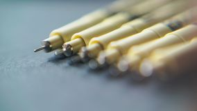 Pens are laying on the table. Macro view with blur effect of gold-plated pens with silvery rods, which lie neatly on the table stock video