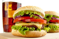 Macro view of cheeseburgers and glass of cola on wooden board Royalty Free Stock Photo