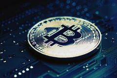 Macro view of a circuit board with a digital bitcoin Royalty Free Stock Photo