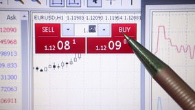 Macro view of currency sales website screen with extreme close up of user pointing at buy and sell figures with mechanical pencil. Fintech describes an stock footage