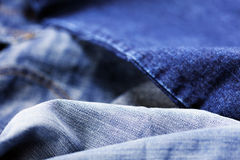 Jeans Macro Background. Macro view of a detail from a pair of blue jeans, on the blurry background of a lighter pare of jeans Stock Photo