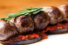 Macro view grilled meatballs on eggplants tomato sauce, rosemary. A dish in a white plate, wooden table background. Close-up soft selective focus stock image