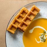 Macro view of pumpkin and carrot soup bowl, with freshly baked Belgian waffle Royalty Free Stock Images