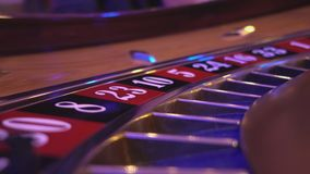 Macro view on a Roulette Wheel in a casino - camera fixed on turning wheel stock video footage