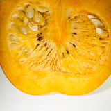 Macro view of a section of orange pumpkin with pulp and seeds Stock Image